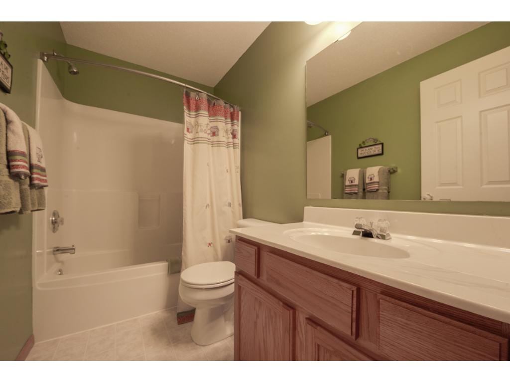 Full bath features a tub/shower combo, oversized single storage vanity and bronze light fixture above.