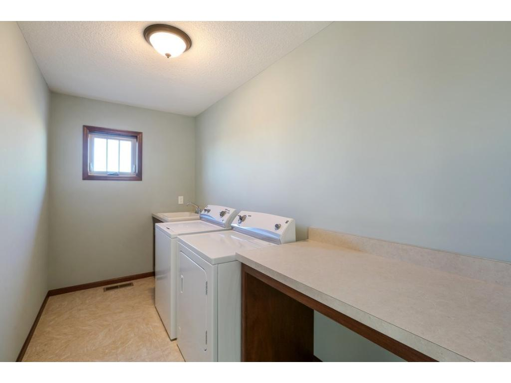 Convenient upper level laundry room - just outside the bedrooms and baths! Note the utility sink PLUS the spacious folding counter with basket storage below!
