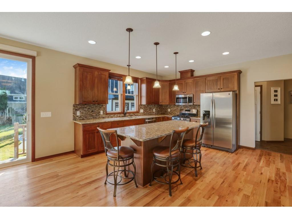 Chef's kitchen includes gorgeous custom cabinetry; stainless steel appliances including gas range; granite counters with tile backsplash; oversized center island with seating; recessed + pendant lighting; large windows above the sink; and more!