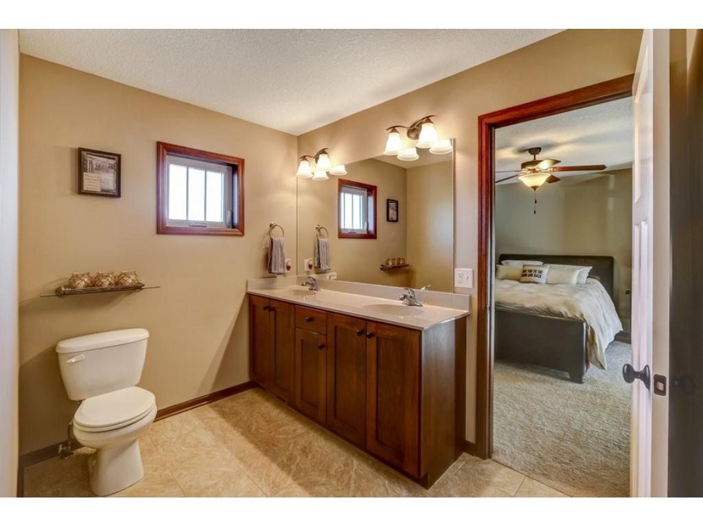 Spacious owner's bath features ceramic tile, raised double vanity, generous walk-in closet, and custom, walk-in shower.