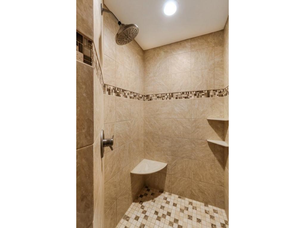 Fantastic walk-in shower features shampoo shelves, shaving bench and neutral custom tile work.