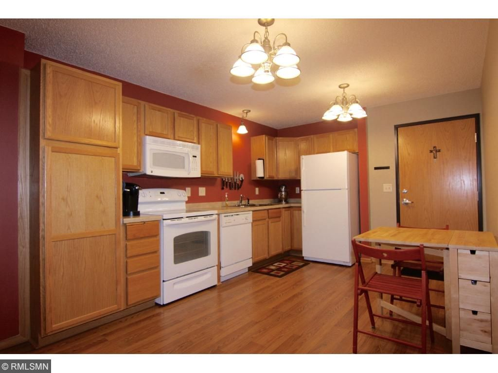 Hardwood laminate flooring and pantry to the left of the stove. The kitchen has good functioning space and it is open to the living room area.