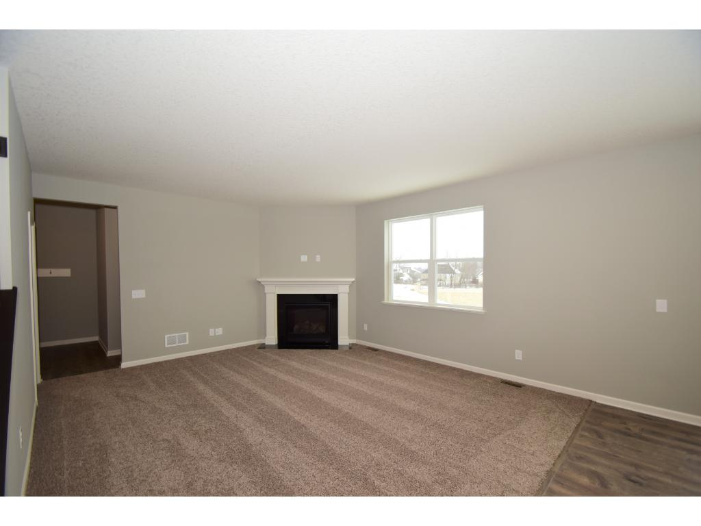 Granite surround gas corner fireplace in living room.  Photos are of same floor plan.  Options and color selections will vary.