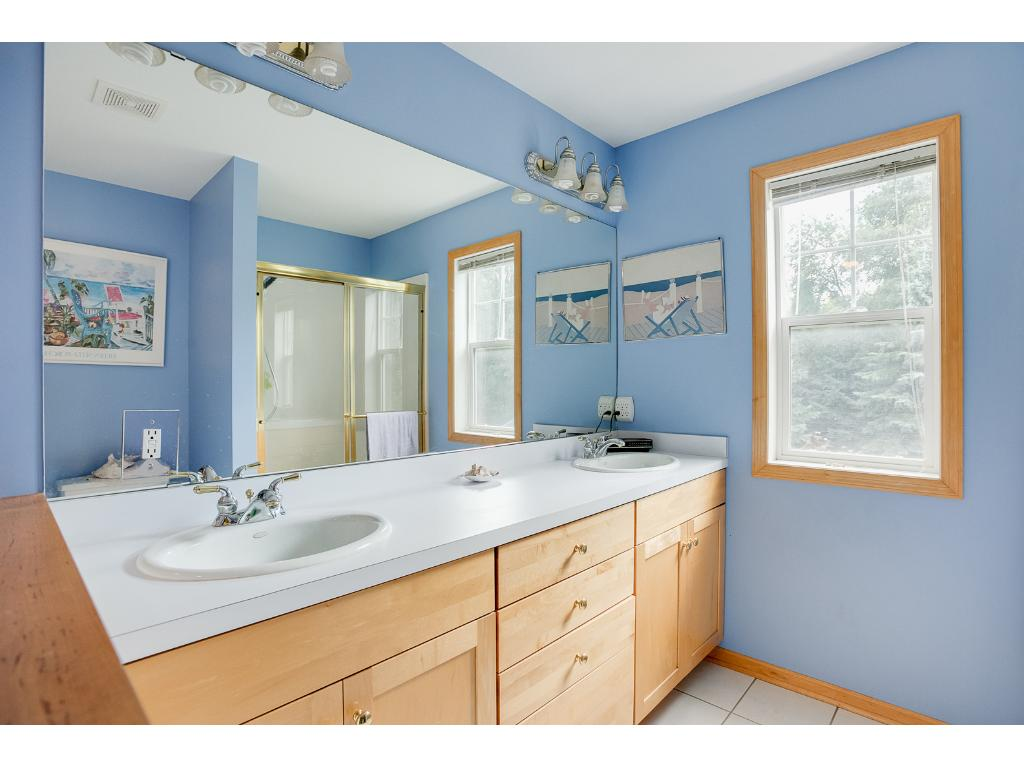 The bathroom features two sinks, a separate shower and tub and plenty of lighting and counter space.
