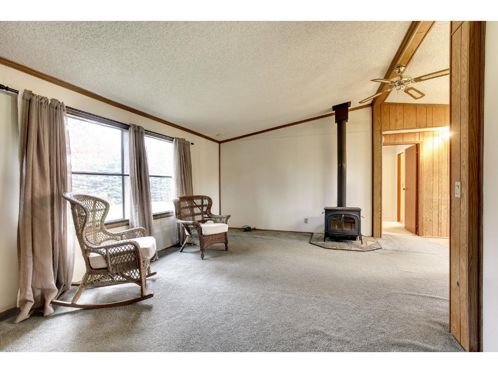 Spacious living room with a fun stove/fireplace.