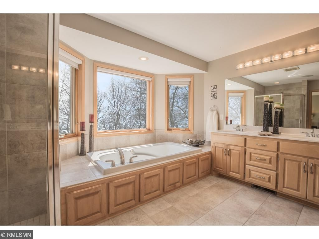 Luxurious master bath offers double sink vanity with maple cabinetry, tile flooring, private water closet, window, linen closet, whirlpool tub and shower.
