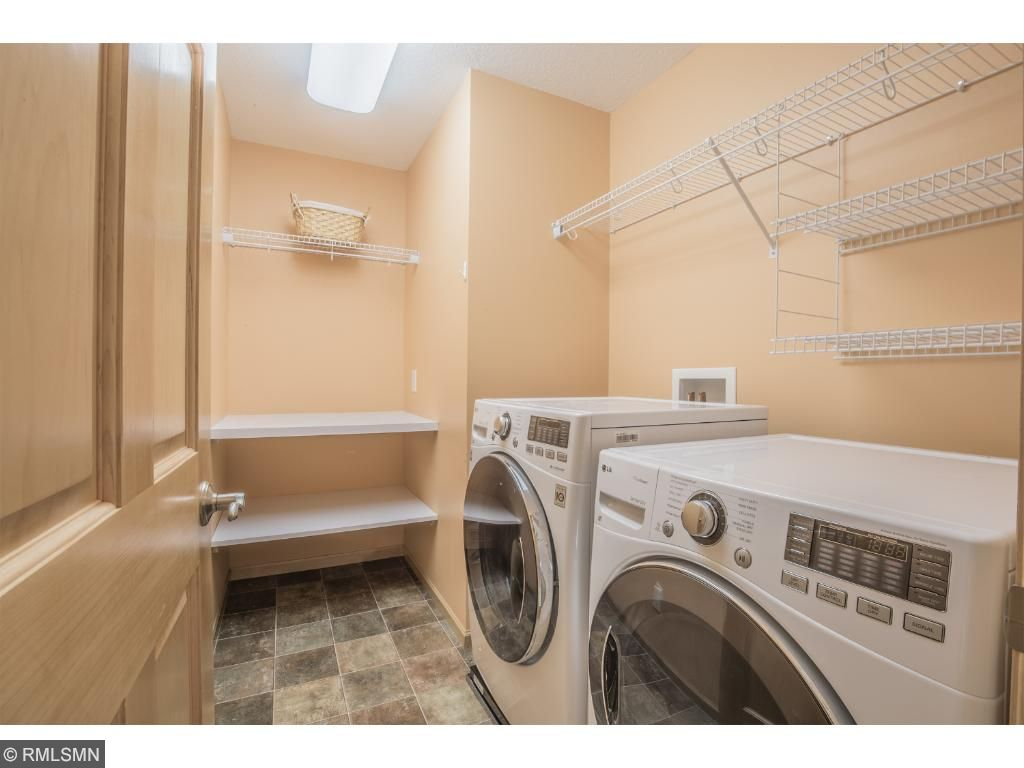 Convenient laundry room offers ample shelving and counter space.