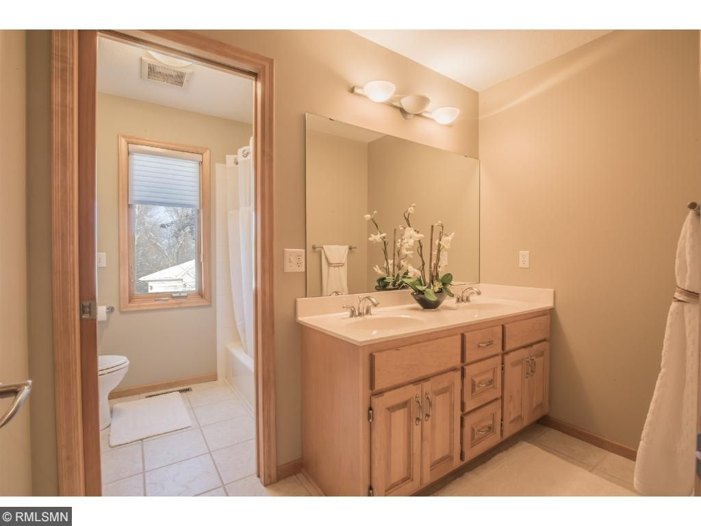 Full bath with tile flooring, maple cabinetry, and private water closet and bath/shower area.