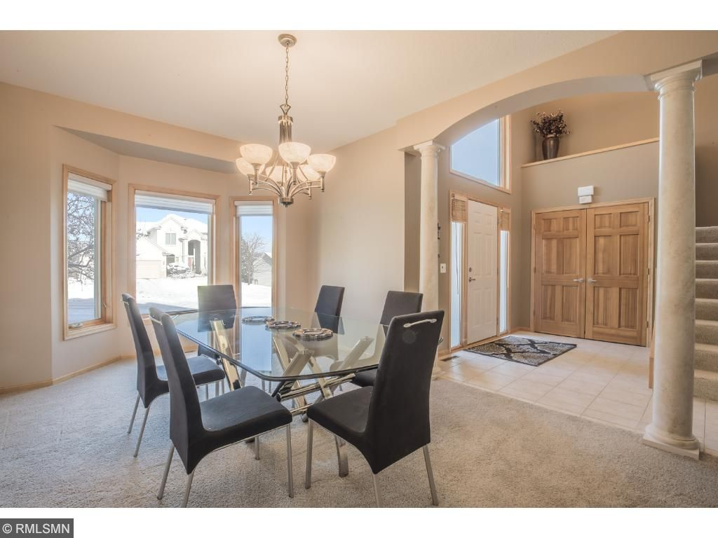 Formal dining room offers elegant pillared arched entry, spacious bowed windows, and front yard views.