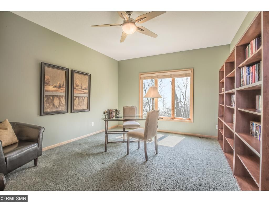 Office includes ceiling fan, French doors, and serene backyard views.