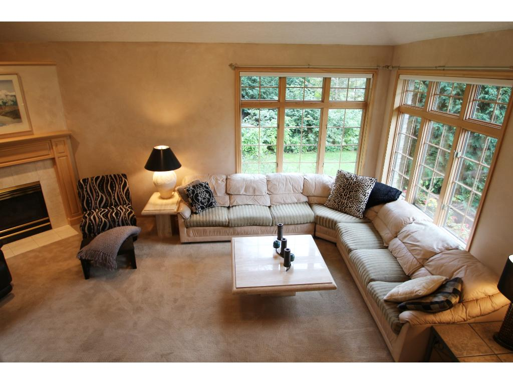Open living room with great natural light pouring in from generous sized windows and patio door!