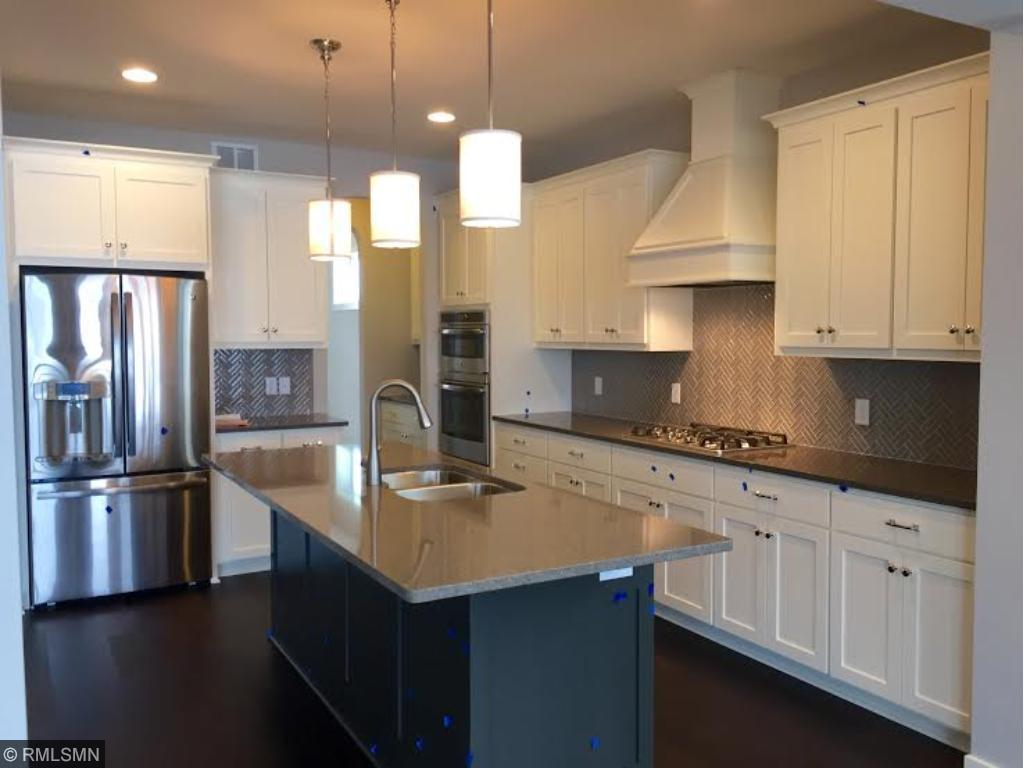 Open kitchen with custom painted cabinetry,  designer tapered wood hood with cook top and custom tile backsplash- picture is of like model materials and finishes may vary.