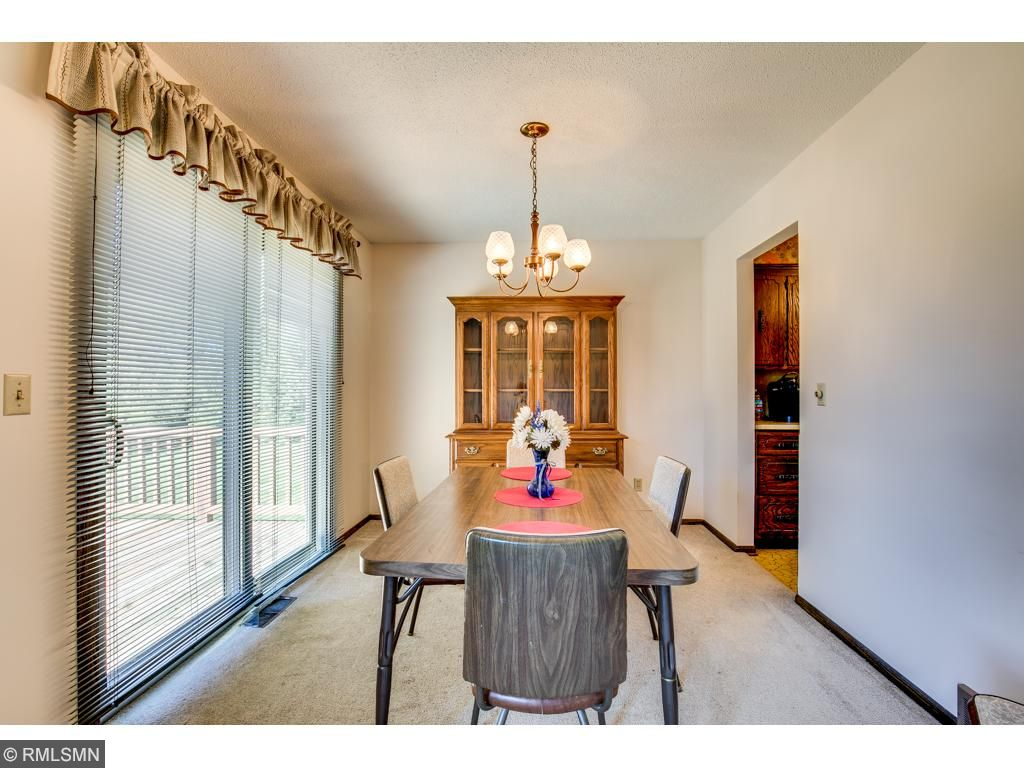 The dining room walks out to a large deck that overlooks the in-ground pool.