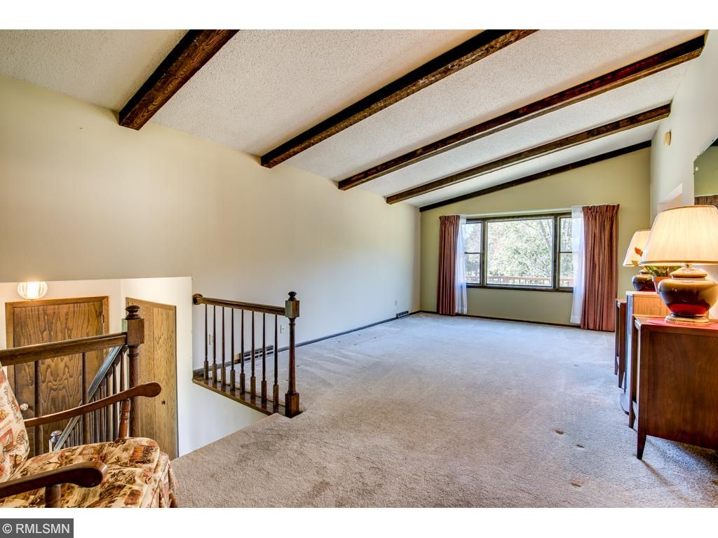 The main level living room has vaulted ceilings and large windows. The dining room walks out to a large deck that overlooks the in-ground pool.