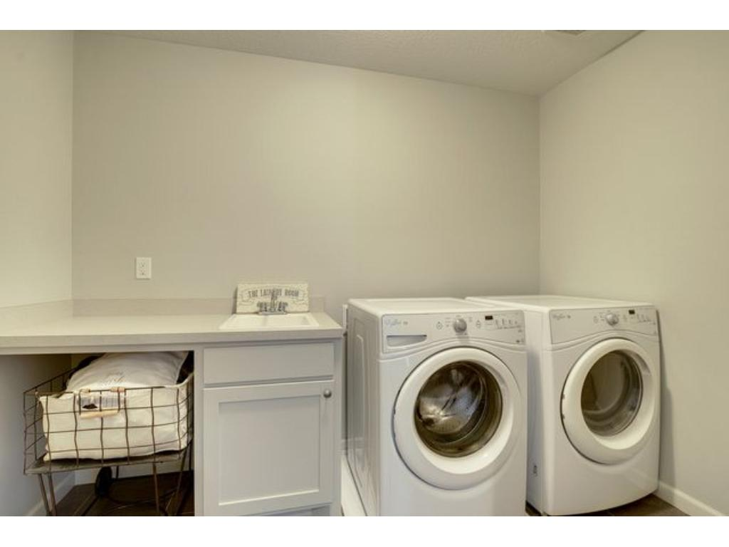 Upper level laundry with sink, high efficient washer and dryer, storage,  folding, and sorting space, make doing laundry much more enjoyable.