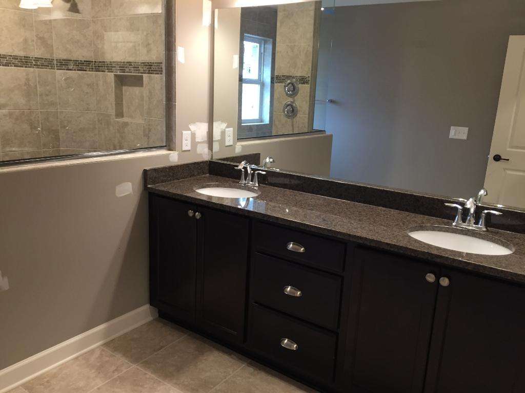 This serenity owners' bathroom has a double vanity with granite countertops. Its best feature is the walk-in shower completed in full tile.