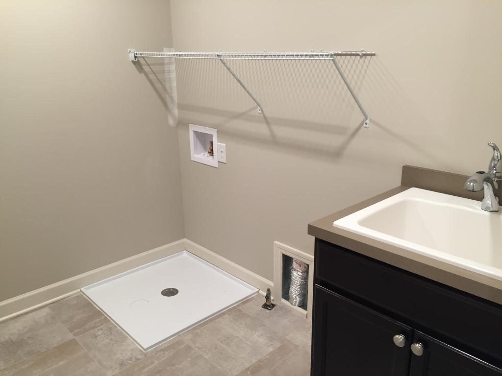 Upper level laundry with a drop-in laundry tub and storage cabinet.