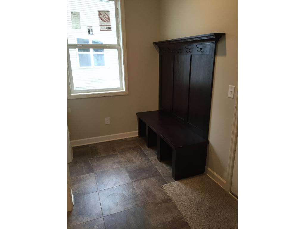 Off the kitchen is this mudroom, featuring a built-in bench with hooks. Not shown but adjoining the mudroom is the main level powder room, perfectly located for coming in from the garage. There is also a very large walk-in closet (next photo).