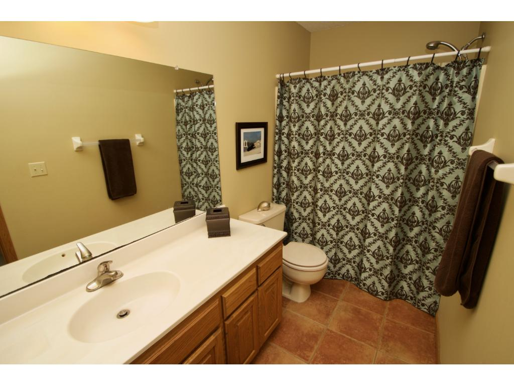 Spacious upper full bath with ceramic flooring, large vanity with drawers and a linen closet outside in hallway for additional storage.