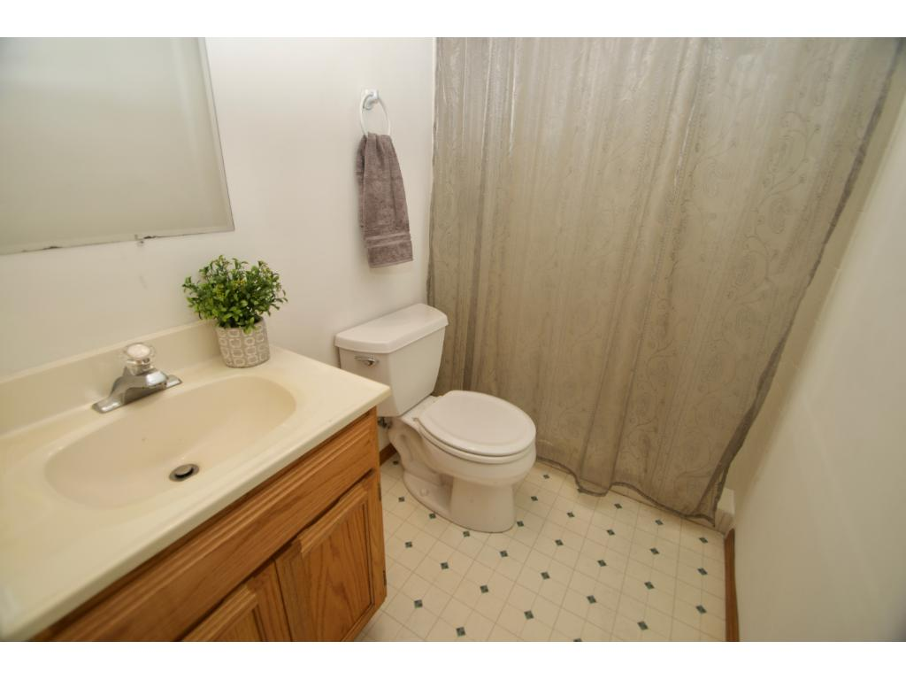Lower level 3/4 bath with tile shower, vanity with storage and is located right off the family room.