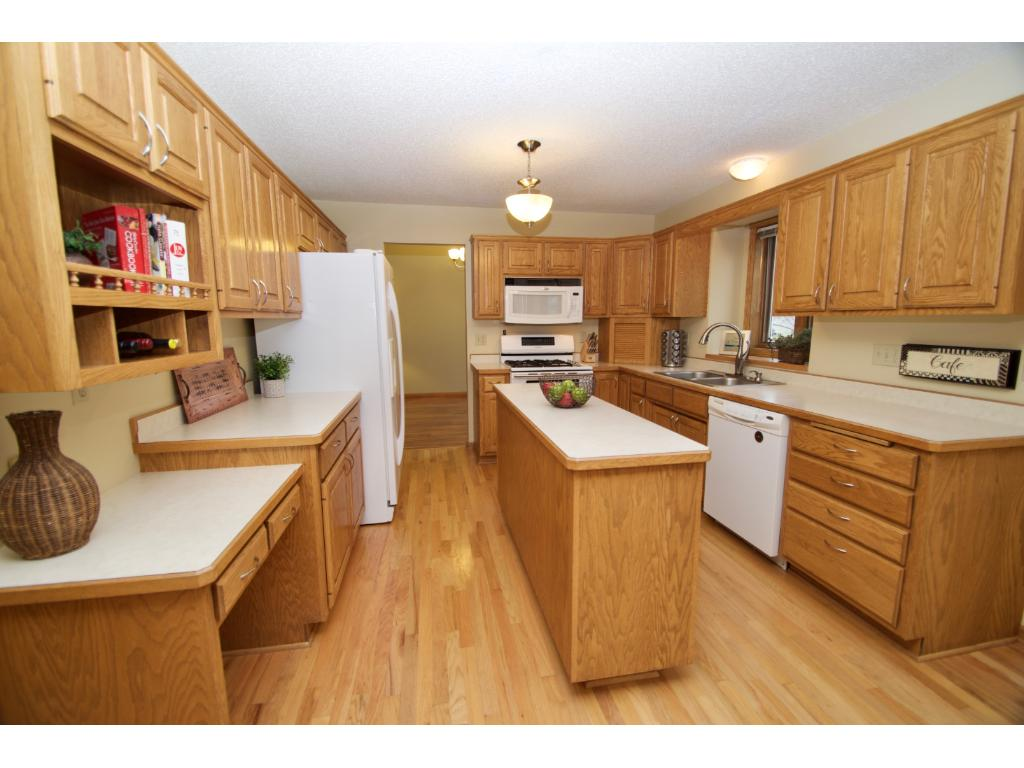 Great functional kitchen offers a double oven, spacious center island with cabinets, real wood flooring, work station, kitchen window and nice cabinet/ counter space.