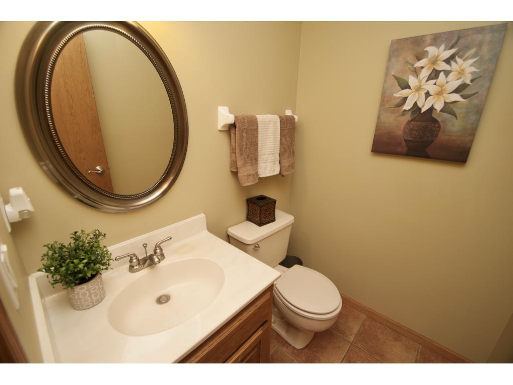 Main floor bath with ceramic flooring and vanity with storage.