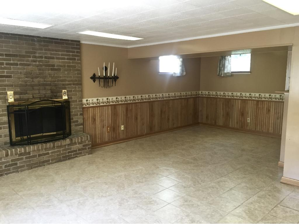 The L-shaped space has a wood burning fireplace, wood paneling and good lighting.
