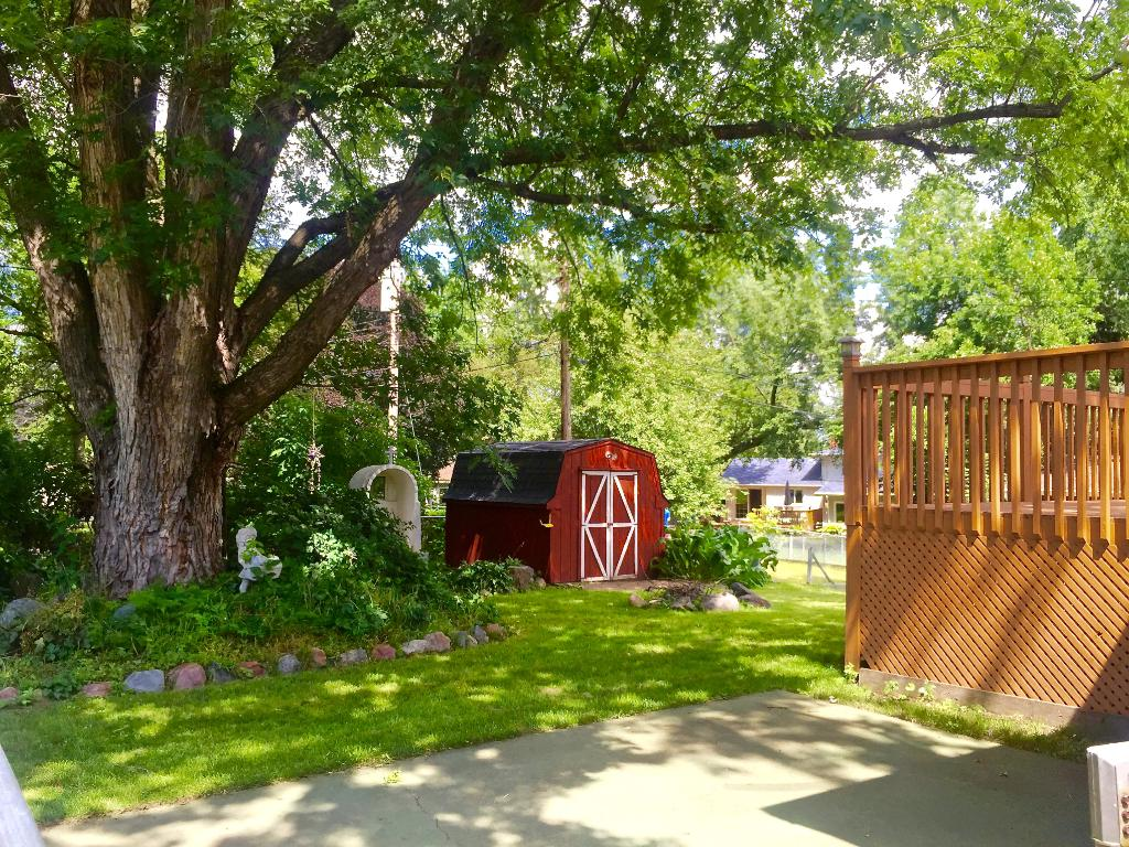 The gorgeous oak tree, gardens, shed and firepit create a serene outdoor living space.