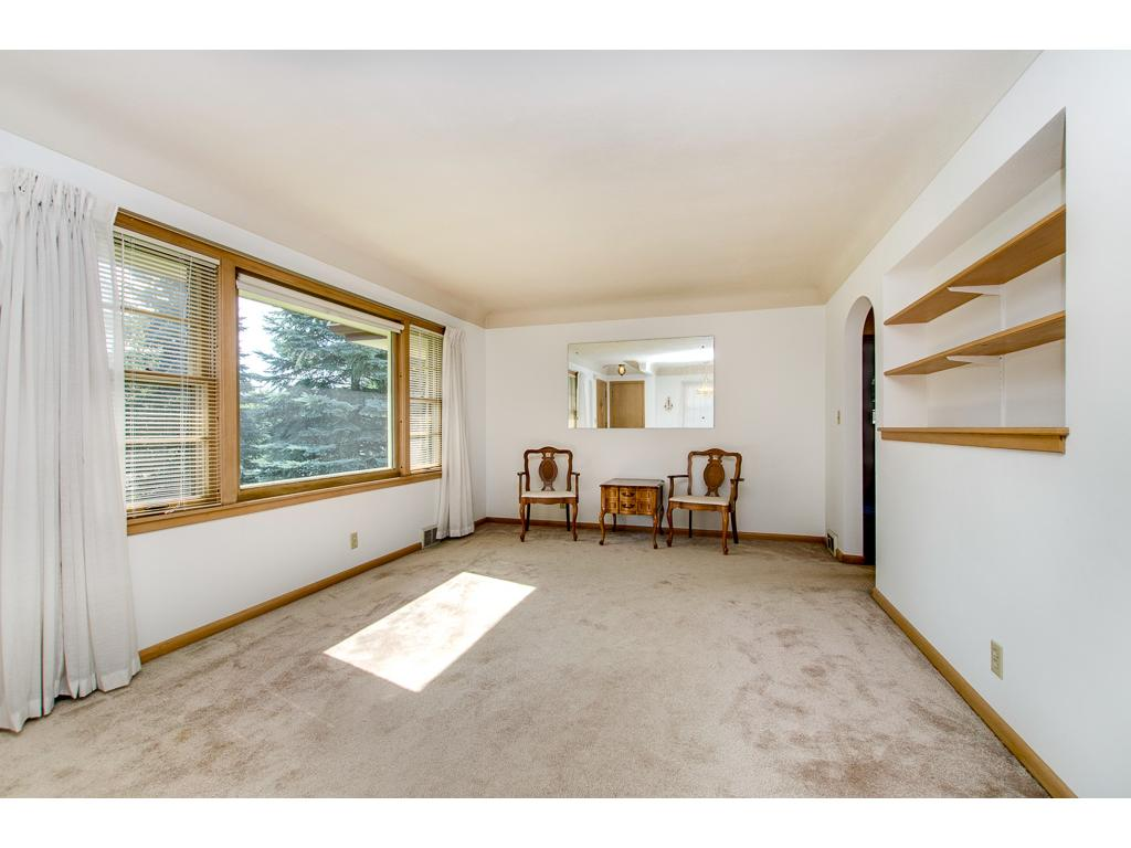 Large Formal Living Room With Picture Window and Built-in Book Shelves---Hardwood Floors Under the Carpet