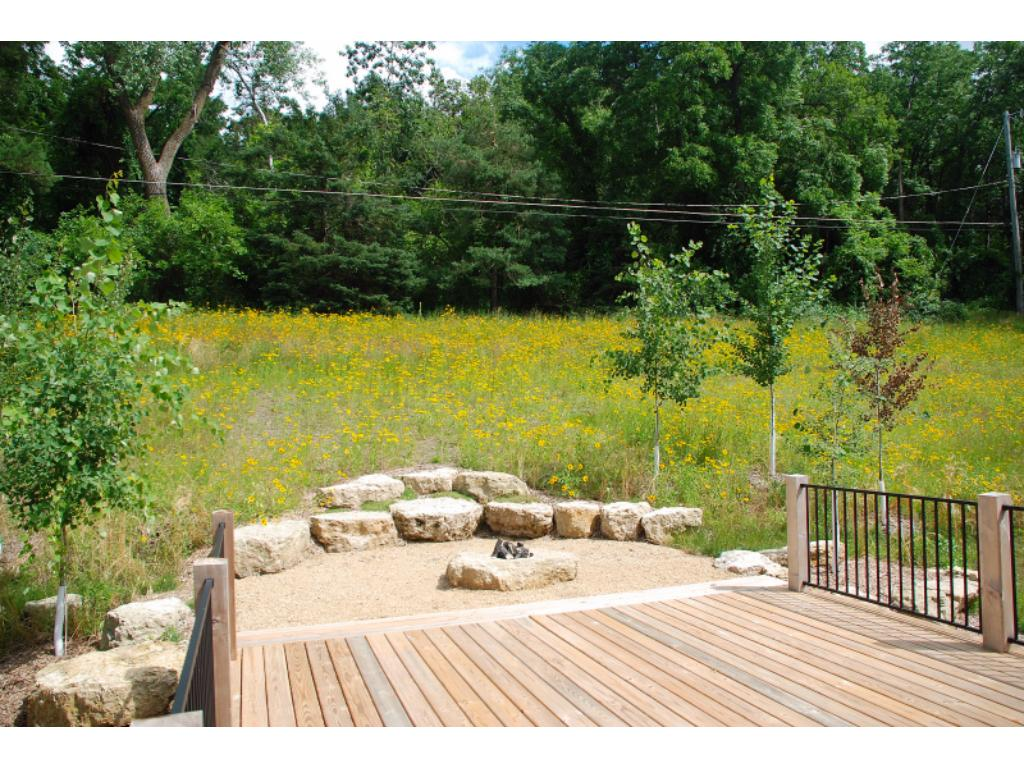 Private deck features a gas fire pit, overlooks back yard planted in prairie grass and wildflowers with wildlife galore right out your windows!