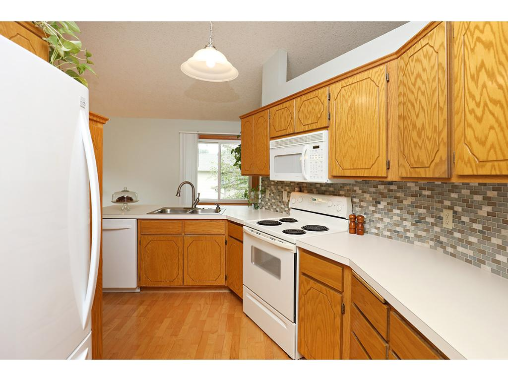 Bright, open Kitchen has matching white appliances and Updated Lighting.