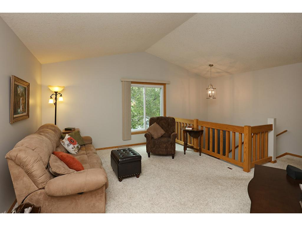 Vaulted Great Room with Open Rails and neutral decor provides the initial welcome to this home.