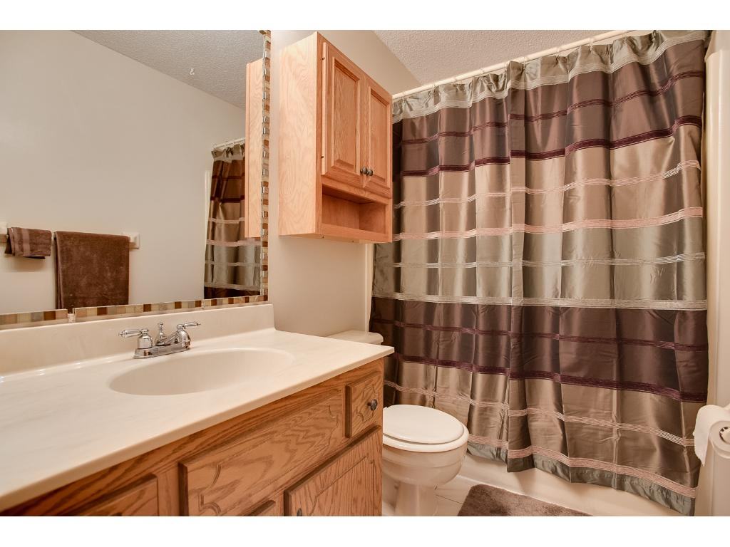 upper level bathroom with tile floors, over the toilet cabinet and tile surround around the mirror