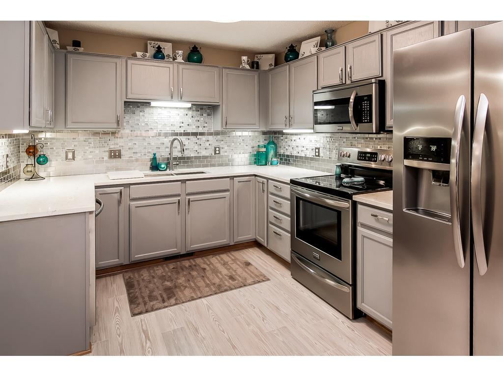 "New quartz kitchen counters and glass tile backsplash, ""fingerproof"" stainless kitchen appliances"