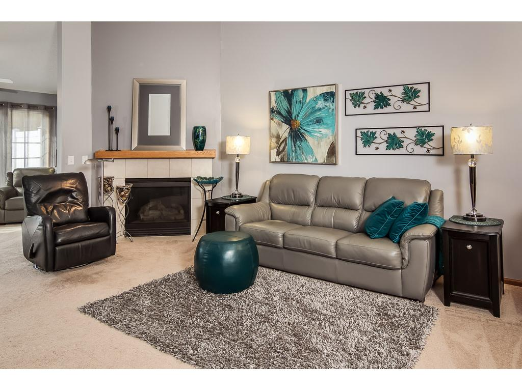 Cozy gas fireplace is a highlight of vaulted living area