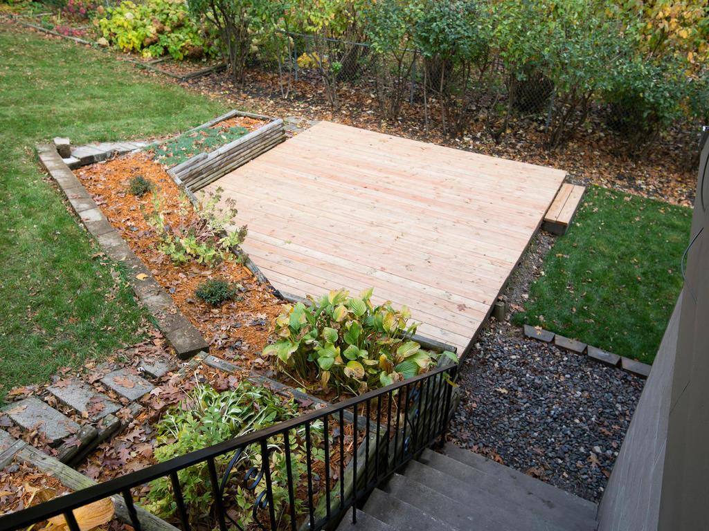 View down to lower deck from patio. Backyard has landscaped garden beds with beautiful large established hydrangea bushes.
