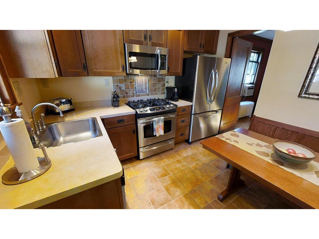 The updated kitchen features stainless steel appliances and custom cabinets designed to match the craftsman detail of the home.