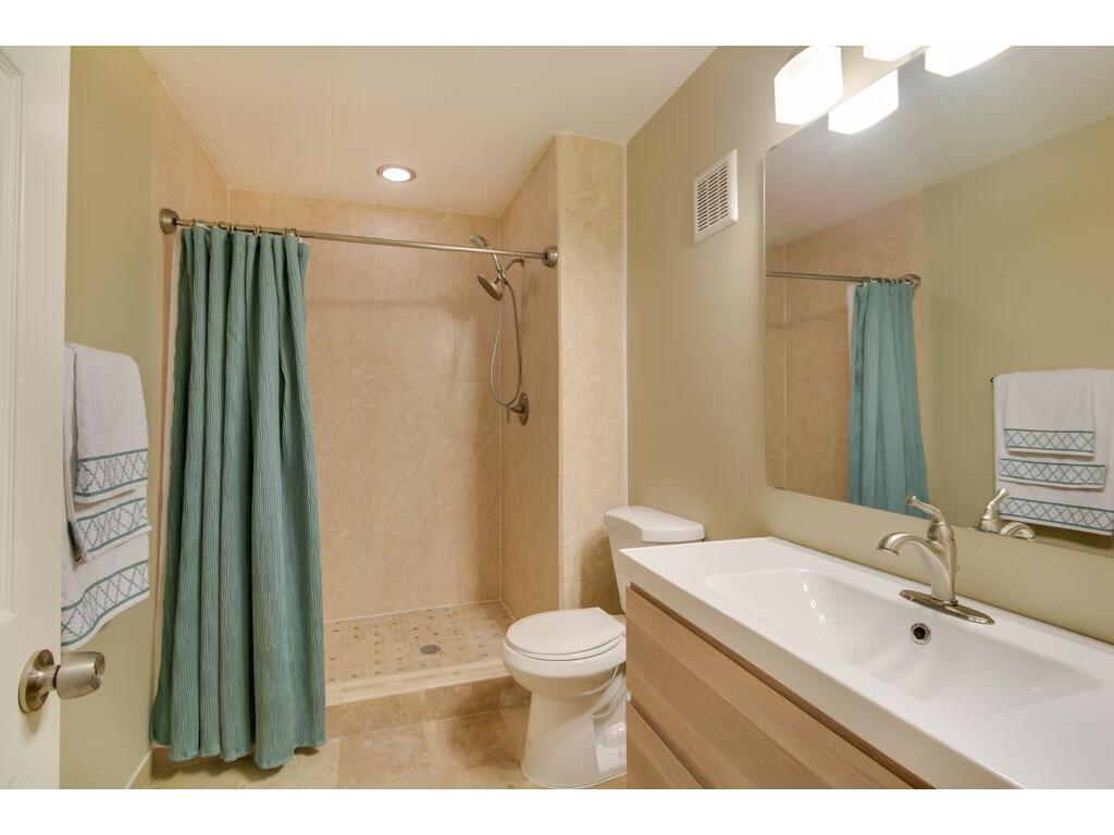 Neutral lower level bath with oversize tile shower.