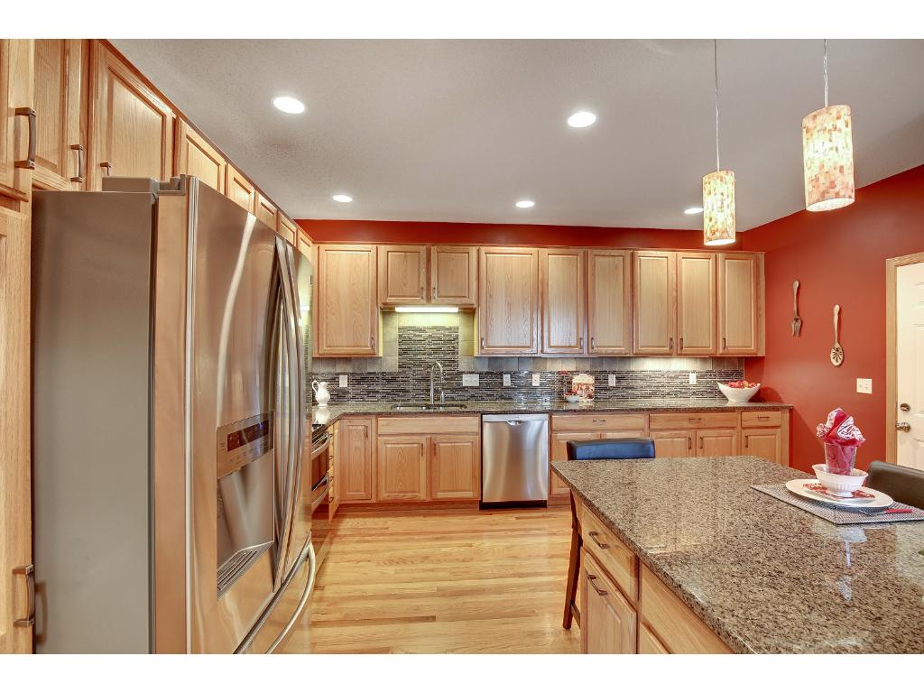 A dream kitchen with granite counter tops and stainless steal appliances.