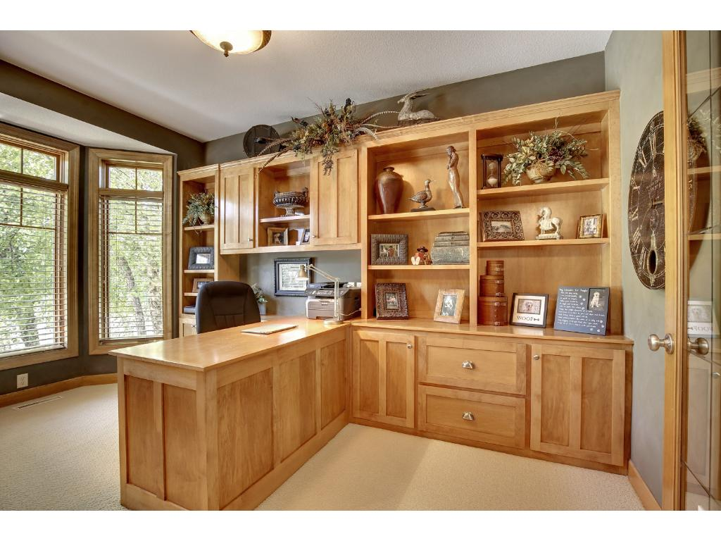 Well appointed, executive home office with French doors is loaded with custom built-ins.