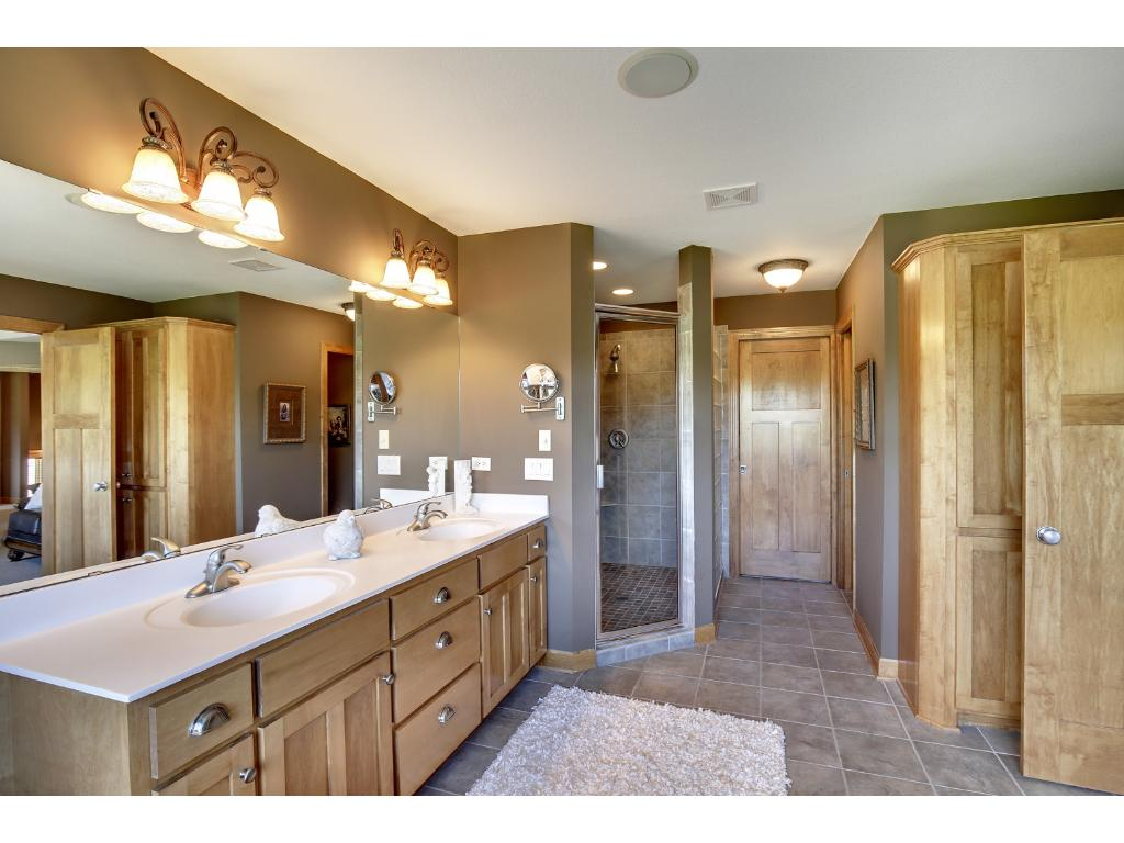 Master bath offers oversized his-and-hers vanities, walk-in shower with glass block detail, private water closet, mounted whirlpool tub surrounded by windows, soft tile flooring, & walk-in closet with organizers. What a retreat!