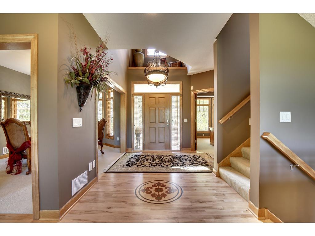Gracious foyer with chandelier and custom tile opens to the heart of the home!