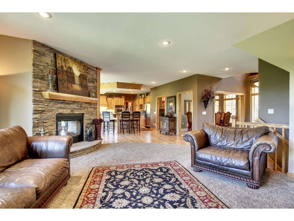 Lovely stone fireplace & built-in media/display cabinets separate the living room from the kitchen area. Note the panoramic views out the expansive rear windows!