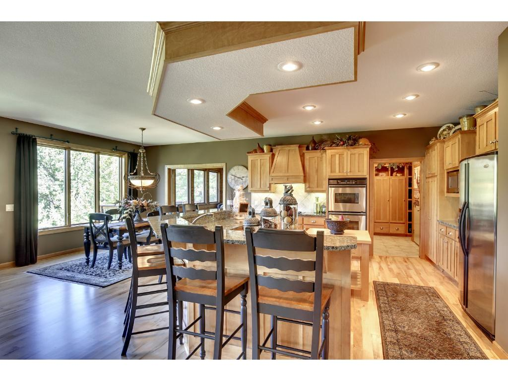 Kitchen is a chef's delight with custom maple cabinets; stone backsplash; granite; center island with raised snack bar; butcher-block prep island; & high-end stainless appliances.