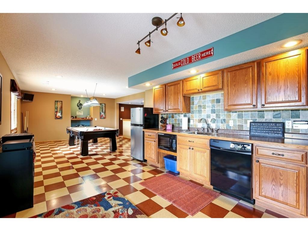The open lower level has a wet bar with a refrigerator and a dishwasher.  That floor is polished Marmoleum!  Plenty of room for entertaining.