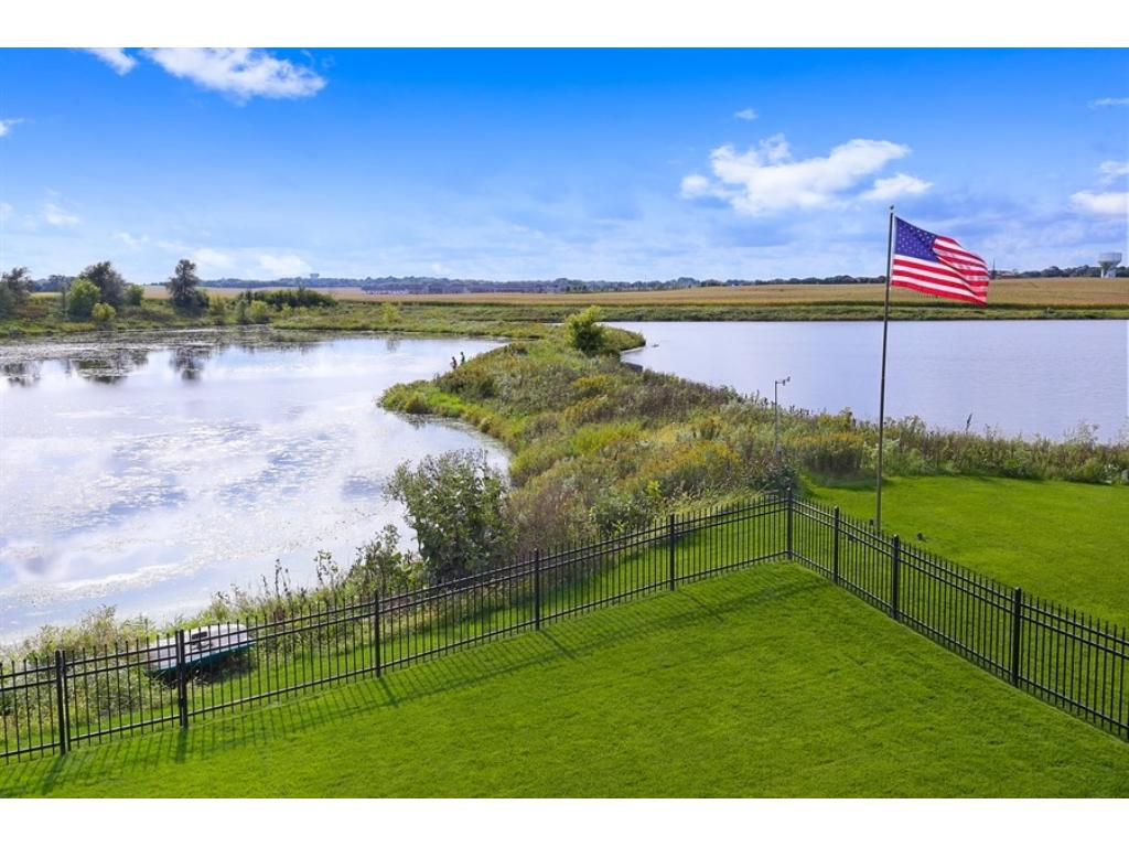 Back yard has enclosing enameled aluminum fence.  The lot actually goes beyond the flag pole to the right.  Fishing and paddle boating!