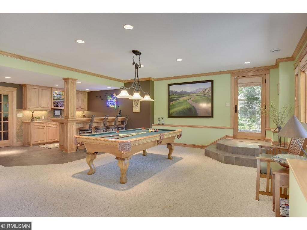 Play a game of pool or enjoy drinks from the wet bar featuring a spiral cork backsplash.