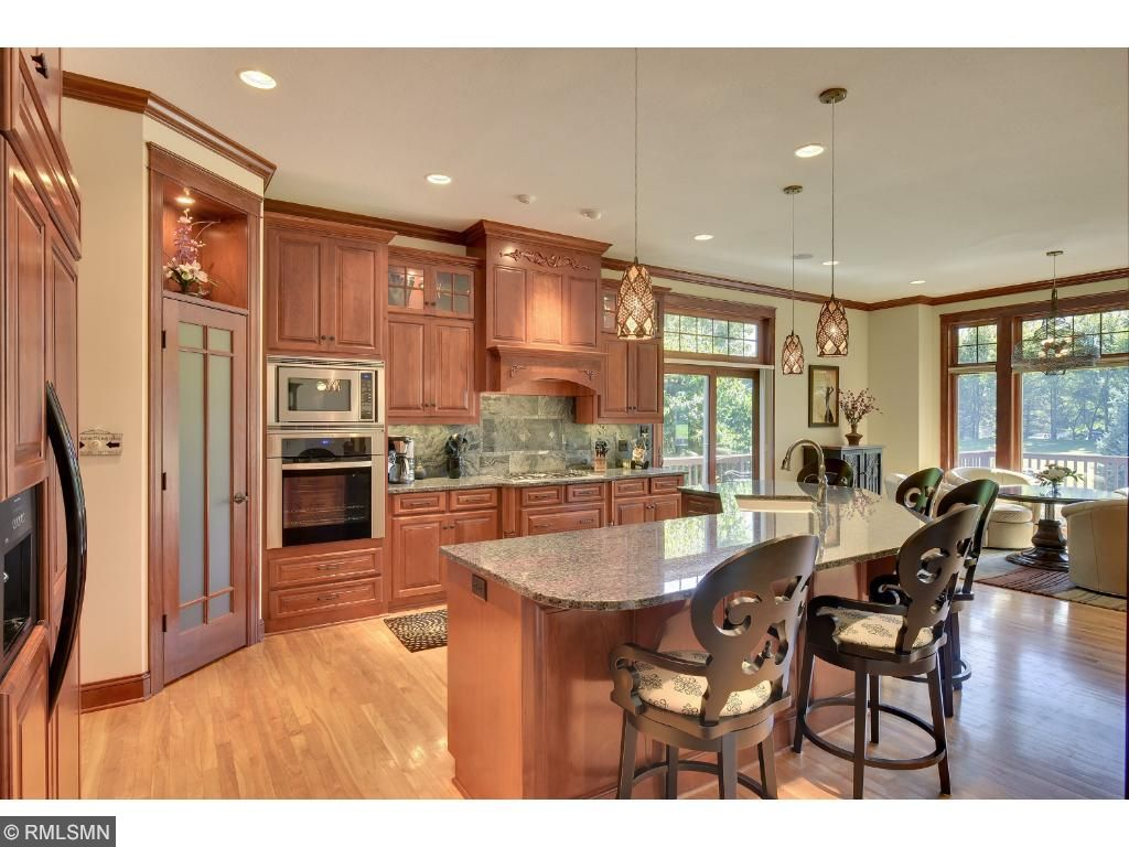 Kitchen is very open with an expansive island that has room for at least 5 people. Matching refrigerator and stainless steel appliances, granite countertops, and marble backsplash.