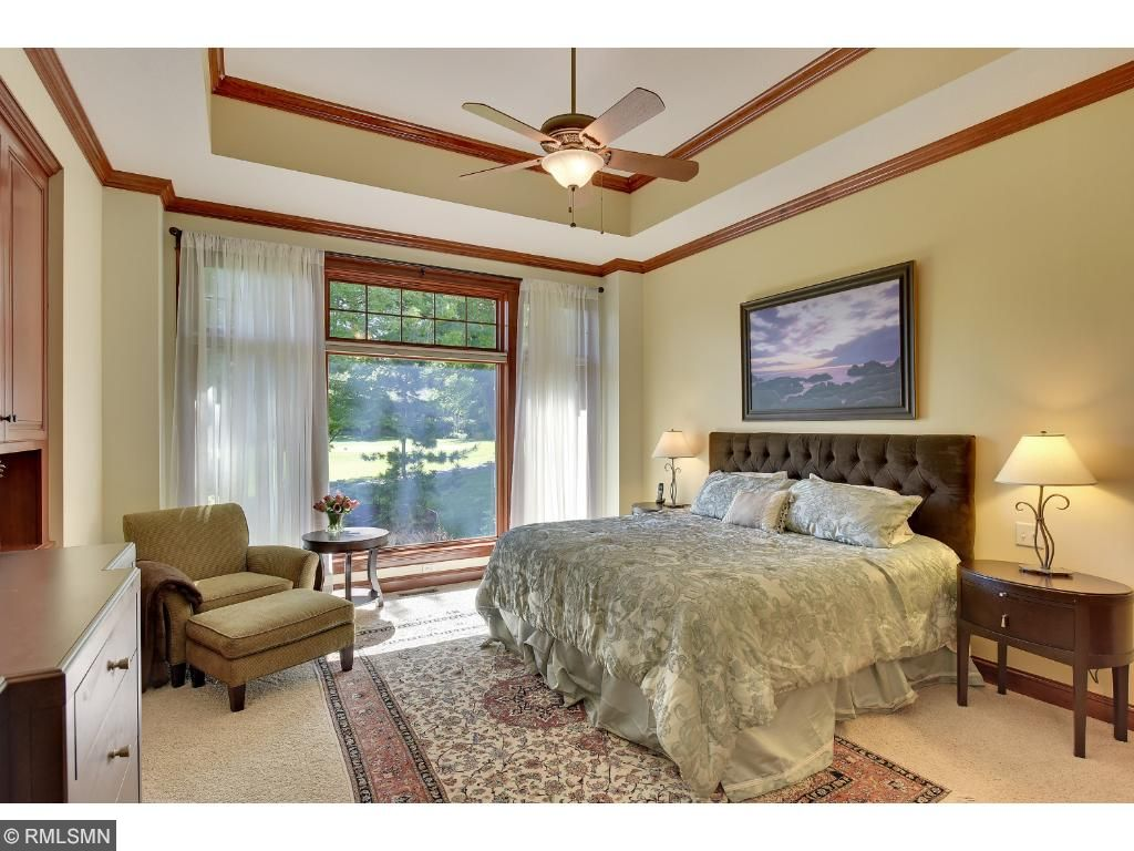 Main level master bedroom with boxed ceilings and a cozy two way fireplace between the room and en suite.