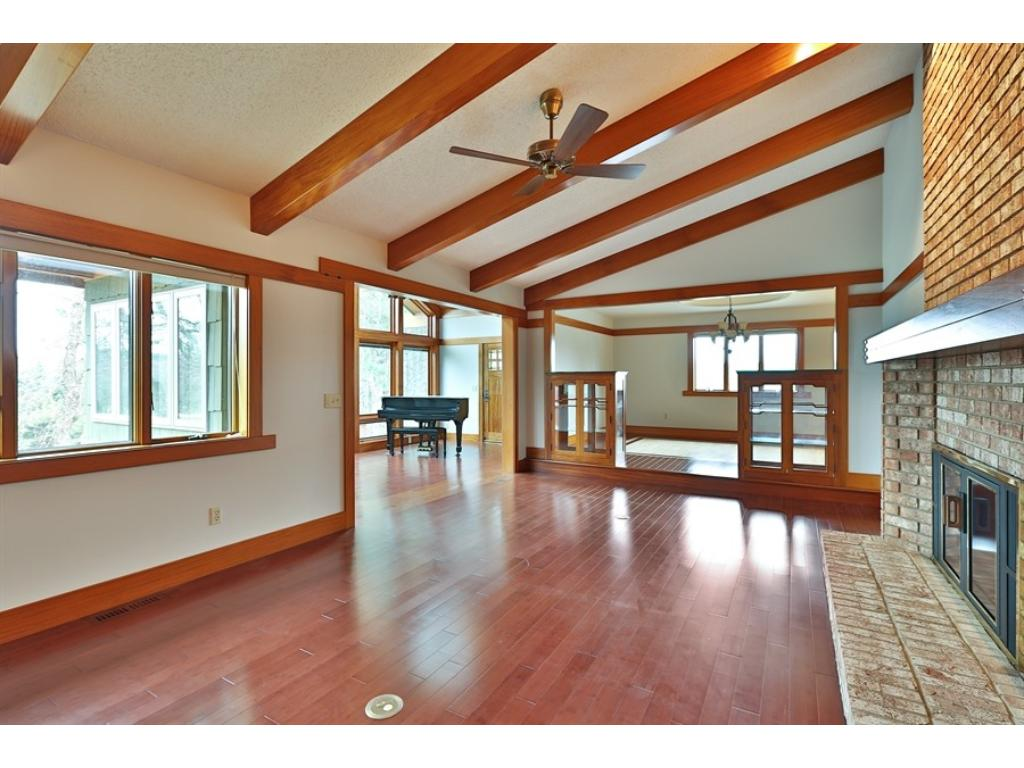 Large living room has gorgeous hard wood floors, floor to ceiling brick fireplace, and ceiling beames wrapped in African Mahogany.
